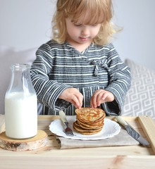 Little Girl Eating Healthy Breakfast in Bed Homemade Banana Pancakes Milk Glass Bottle Wooden Table Cushion Interior Toned Copy Space White Sheets Eco Style Indoor