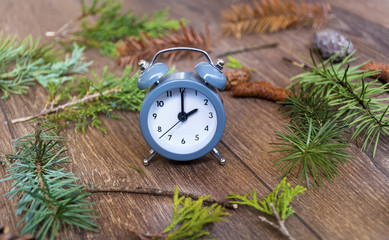 Fall Back Time - Daylight Savings End - Return To Winter Time.Autumn leaves and vintage clock on a wooden background
