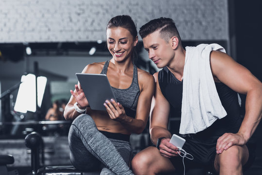 couple using tablet in gym