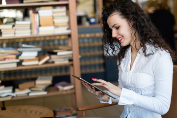 Young woman using digital tablet in coffee shop
