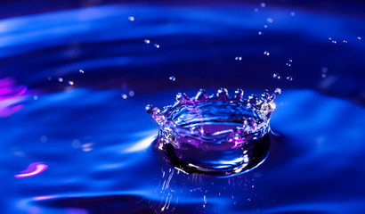 Water drop falling into water making a crown