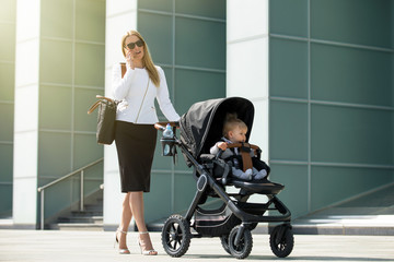 Business woman talking on the phone and pushing baby stroller