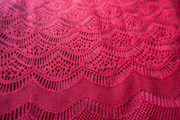 Curvilinear geometric pattern on red lacy fabric