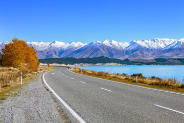 Scenic Road along Lake Tekapo  at beautiful  sunny morning . .Lake Tekapo and mountains with snow in autumn,  Canterbury, South Island, New Zealand.