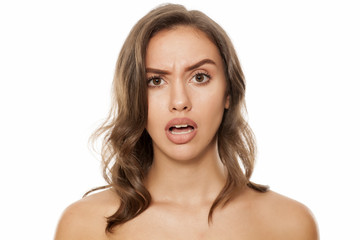 Portrait of beautiful young surprised woman on white background