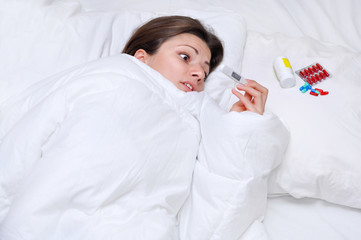 Sick young woman lying with thermometer in white bed. feel the pain