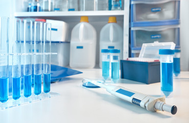 Scientific background, closeup on automatic pipette with laboratory out of focus