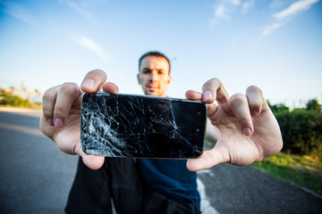 Men's hands hold a smartphone with a cracked screen