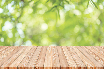 Wood table top on blur green abstract background from nature, can be used for display or montage your products.