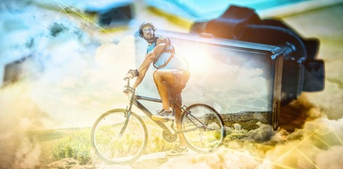 Composite image of fit man cycling on rocky terrain