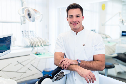 Attractive male dentist in doctors white lab coat posing in modern dental office