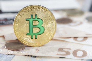 Cryptocurrency physical green bitcoin coin over the euro money.