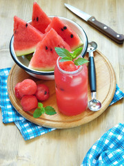Watermelon segments and a refreshing drink with ice and decorated with mint