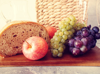 Fresh fruit and bread with the picnic basket in background