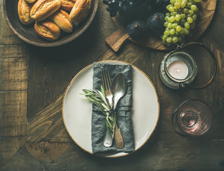 Fall holiday table decoration setting. Plate with linen napkin, fork and spoon, candle, fresh fruits on serving board, bread buns, olive tree branch over wooden background, top view, copy space