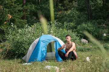 Camping in the mountains. A man sits near tent against the backdrop of green trees and mountains.