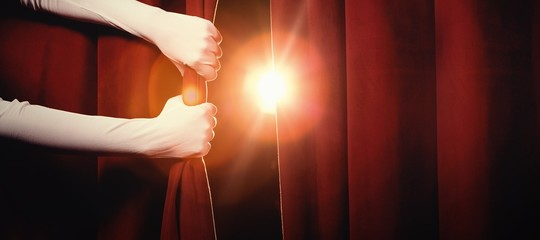 Cropped hands holding curtain at stage