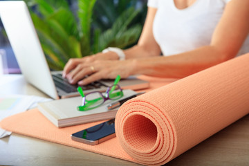 Woman and an exercise mat in an office background
