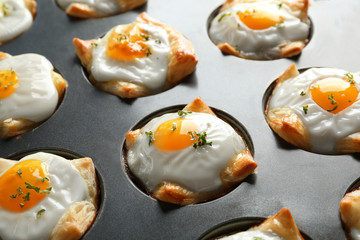 Baking mold with tasty eggs in dough, closeup