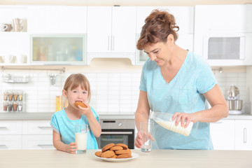 Cute little girl and her grandmother tasting cookies on kitchen