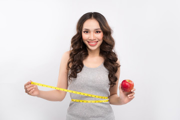 Woman measuring her waistline and holding apple. Weight losing concept.