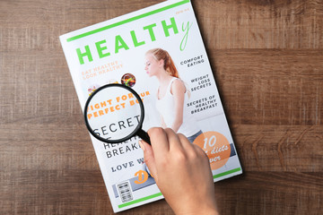 Woman holding magnifying glass over magazine. Search concept