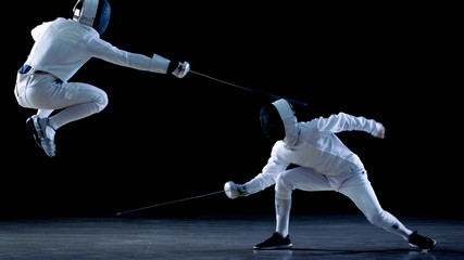 Two Professional Fencers Show Masterful Swordsmanship in their Foil Fight. They Dodge, Leap and Thrust and Lunge. Shot Isolated on Black Background.
