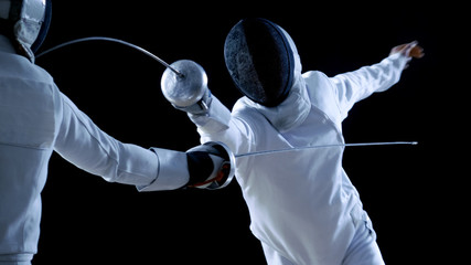Two Professional Fencers Show Masterful Swordsmanship in their Foil Fight. They Attack, Defend, Leap and Thrust and Lunge. Shot Isolated on Black Background.