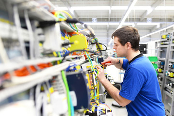 Montage von Elektronik im Maschinenbau - Arbeiter in einer Hi Tech Fabrik // Assembly of electronics in mechanical engineering - workers in a hi-tech factory