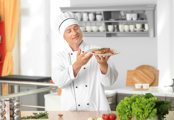 Male chef holding plate with cooked meat in kitchen