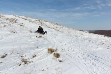 Man in a black jacket riding a mountain on a plastic sled in winter, Russia, Bugotak Hills