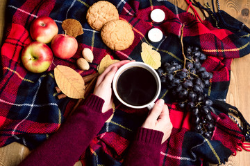 Hand keeping cup of coffee Apple Cookies Cinnamon Grape Wooden background Autumn blanket Autumn lifestyle concept Top view