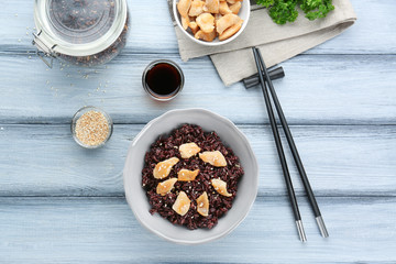 Plate with black rice on wooden table