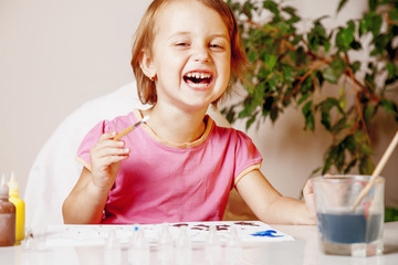 beautiful happy little kid girl laughing and drawing a picture paints (postmodernism, talent, creativity, creativity)