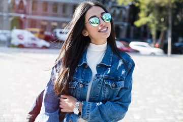 Close up fashion portrait of attractive woman in jeans with long dark hair.Girl in jeans suit.Charming lady with new denim outfit. Happy young woman in city street