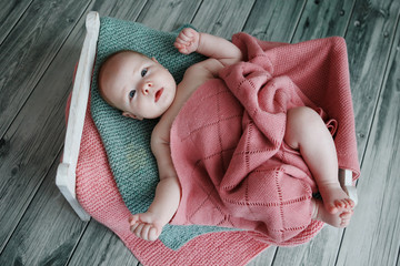 charming and sweet a newborn is covered with a knit blanket in a hand made wooden bed on the green background wooden parquet