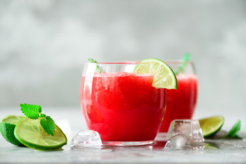 Glass of fresh watermelon juice with lime, mint, ice on light background, copy space