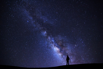 Landscape with milky way galaxy, Starry night sky with stars and silhouette of a standing man on high mountain.