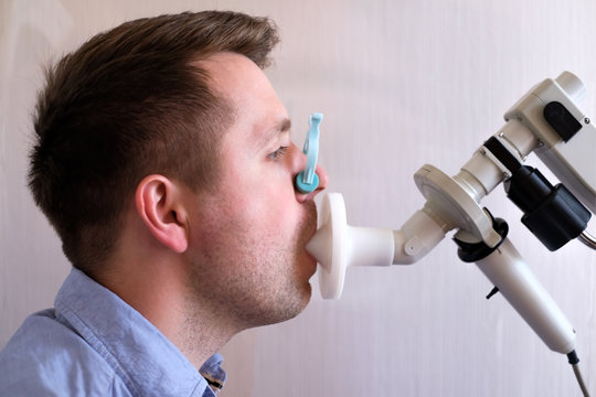 Young man testing breathing function by spirometry
