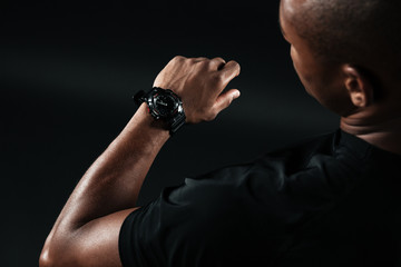 Cropped image of young afro american man, looking at watch
