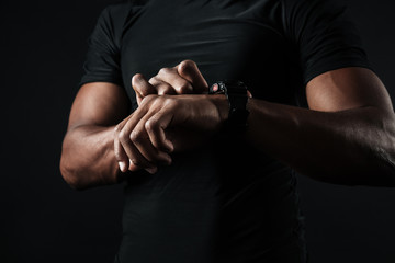 Close-up photo of african man in black t-shirt check out time at black wristwatch