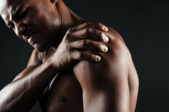 Cropped photo of young shirtless afro american man with shoulder pain