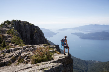 Fit and Adventurous Latin American man is hiking on top of a mountain ridge with a beautiful ocean view in the background. Taken at Lions Peaks, North of Vancouver, British Columbia, Canada.
