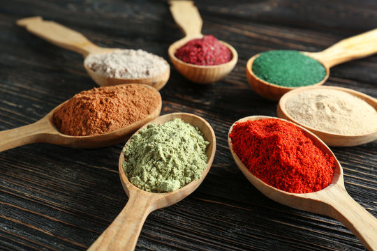 Different colorful superfood powders in spoons on wooden table