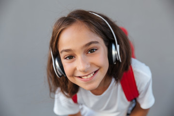 Close up image of smiling brunette schoolgirl listening music