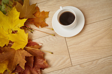 Cup of coffee with yellow autumn leaves on wooden background, top view, with blank copy space