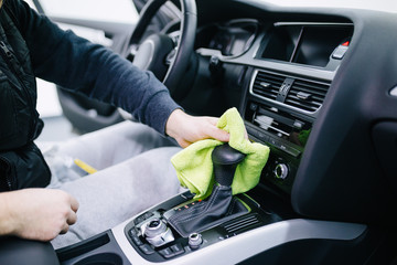 A man cleaning car interior, car detailing (or valeting) concept. Selective focus.