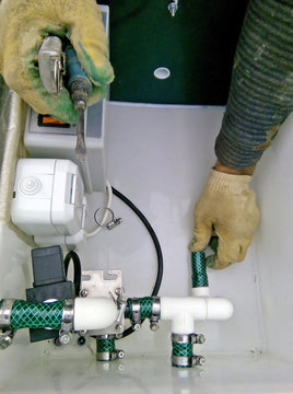 Plumbing building contractor repairing plastic pipe in waste treatment tank (septic system)
