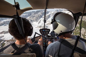 Instructor teaching student how to land helicopter in the alpine terrain.
