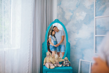 Happy husband and pregnant woman expecting birth sitting on a couch in the interior studio. Man in a denim shorts woman in a denim combination